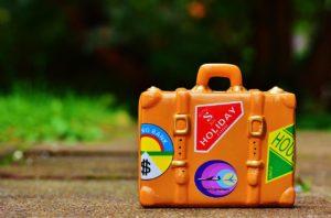 Orangener Koffer mit Stickern steht für Urlaub und Freizeit