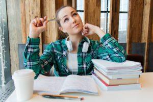 Erwachsenes Mädchen sitzt in einem Cafe, lernt und denkt über Ihre Zukunft nach.
